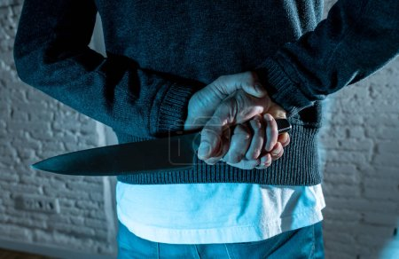 close up of a man holding a knife. dangerous man standing in the dark in London knife crime concept.