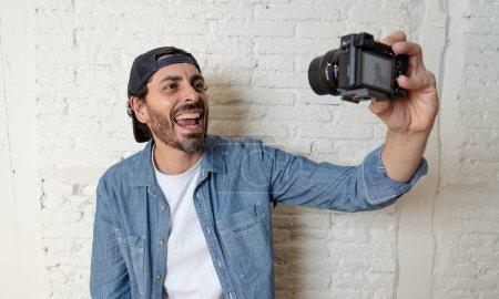 Photo pour Jeune homme séduisant, porter des vêtements décontractés en tenant l'appareil photo autoportrait de tir ou l'enregistrement vidéo en concept de blog et blogger internet du look moderne style hipster. - image libre de droit
