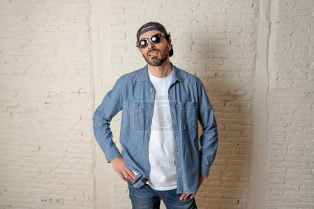 young attractive hipster,  trendy style looking man smiling happy posing cool with attitude dressing informal wearing casual hat.  male fashion concept.