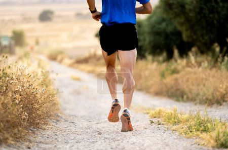 close up man runner legs and feet of extreme cross country man running and training on rural track jogging at sunset with harsh sunlight and lens flare in countryside sport and healthy lifestyle.