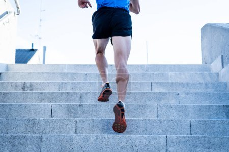 Photo for Man runner running on stairs in urban city sport training young male jogger athlete training and doing workout outdoors in city. Fitness and exercising outdoors urban environment concept. - Royalty Free Image