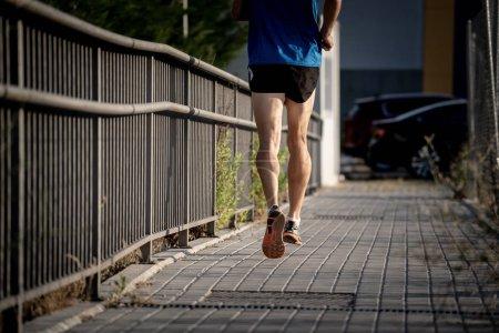 Photo pour Gros plan du sport mans jambes en cours d'exécution avec sport fond urbain ville décor au concept de remise en forme de coureur avec espace copie - image libre de droit
