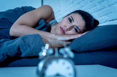 Photo for Young beautiful hispanic woman at home bedroom lying in bed late at night trying to sleep suffering insomnia sleeping disorder or scared on nightmares looking sad worried in mental health concept - Royalty Free Image