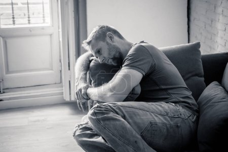 Photo for Unhappy depressed caucasian male sitting and lying in living room couch feeling desperate a lonely. In stressed from work, anxiety, heartbroken and depression concept - Royalty Free Image