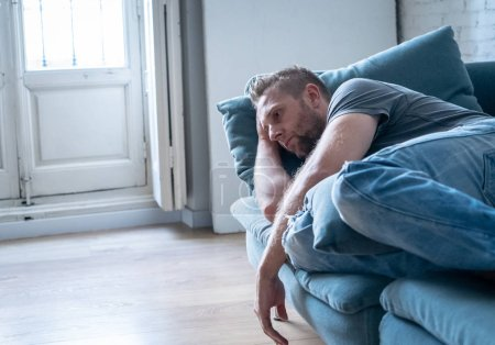 Photo for Unhappy depressed caucasian male sitting and lying in living room couch feeling desperate a lonely. In stressed from work, anxiety, heartbroken and depression concept. - Royalty Free Image