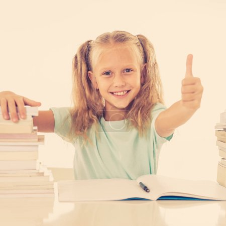 Photo for Happy beautiful cute little schoolgirl likes studying and reading books - Royalty Free Image