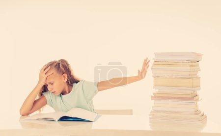 Photo pour Fillette en colère avec une attitude négative envers les études et l'école après avoir étudié trop et ayant trop de devoirs sur fond blanc. Concept de l'éducation des enfants - image libre de droit