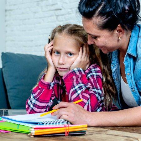 Photo pour Douce maman avec fille incapable de se concentrer tout en faisant les devoirs assis sur le canapé à la maison - image libre de droit