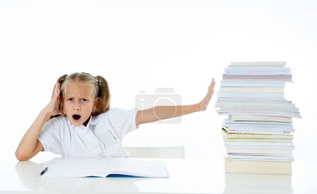 Photo for Frustrated little schoolgirl feeling a failure unable to concentrate in reading and writing. Learning problem and low academic performance concept - Royalty Free Image