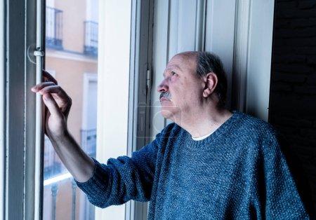 Photo pour Senior homme son sentiment désespéré à la recherche triste tout au long du balcon inquiet déprimé réfléchie et solitaire à domicile de vieillissement dépression mentale problèmes personnels de santé et de la notion de style de vie des années 60. - image libre de droit