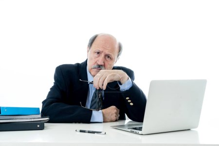 Angry and tired mature businessman overworked at desk not understanding laptop in Older adults perception and use of technology Overtime stress and overwork concept isolated in white background