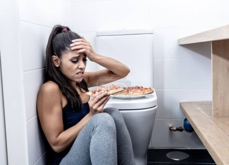 Photo for Attractive young and sad bulimic young woman feeling guilty and sick eating while sitting on the floor next to the toilet in eating disorders anorexia and bulimia concept. - Royalty Free Image