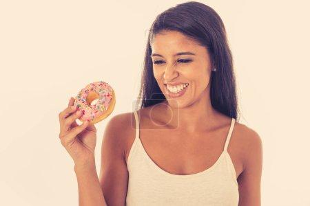 Photo pour Portrait d'extrêmement heureux belle latine jeune femme manger un délicieux beignets en profiter avec plaisir de vous donner un régal et la notion de diète oublier. - image libre de droit