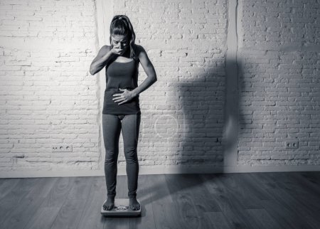 Photo for Young fit and slim woman checking body weight on scale finding herself fat and feeling depressed and desperate with big edgy shadow light in eating disorder and dieting concept. - Royalty Free Image