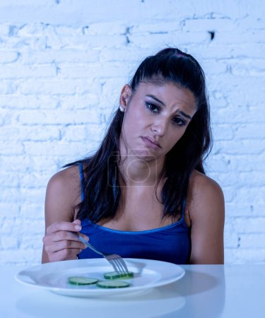 Photo for Portrait o f young attractive woman feeling sad and bored with diet not wanting to eat vegetables or healthy food in Dieting Eating Disorders and weight loss concept. - Royalty Free Image