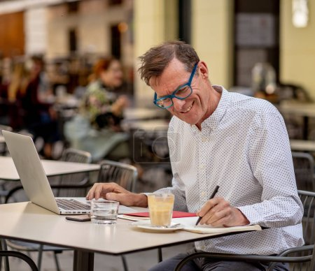 Photo for Cheerful smiling old man working on computer while having coffee in terrace coffee shop city outdoors in seniors using modern technology Staying connected and entrepreneur creative business concept. - Royalty Free Image