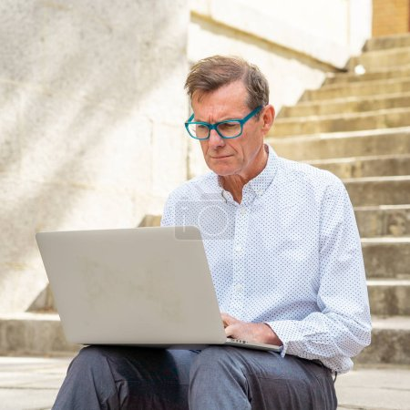 Photo pour Vieil homme élégant travaillant sur ordinateur portable surfer sur Internet assis sur les escaliers à l'extérieur de la ville en nomade numérique Senior en utilisant la technologie moderne Rester connecté et entrepreneur concept d'entreprise créative . - image libre de droit