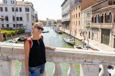Photo pour Jolie femme de tourisme naturel pour latine posant et en regardant la caméra avec des lunettes de soleil au canal à Venise en été vacances voyager autour de concept Europe. - image libre de droit