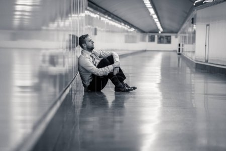 Photo for Young jobless business man suffering depression sitting on ground street underground leaning on wall alone looking desperate in Emotional pain Mental health Unemployment and Human emotions concept. - Royalty Free Image
