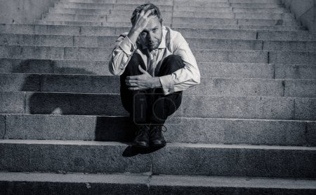 Photo for Young fired business man lost in depression crying abandoned sitting on ground street concrete stairs suffering emotional pain sadness in grunge lighting. - Royalty Free Image