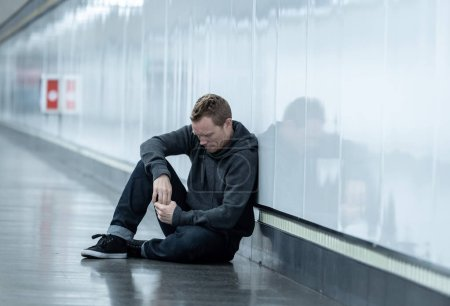 Photo for Miserable jobless young man crying Drug addict Homeless in depression stress sitting on ground street subway tunnel looking desperate leaning on wall alone in Mental disorder Emotional pain Sadness. - Royalty Free Image