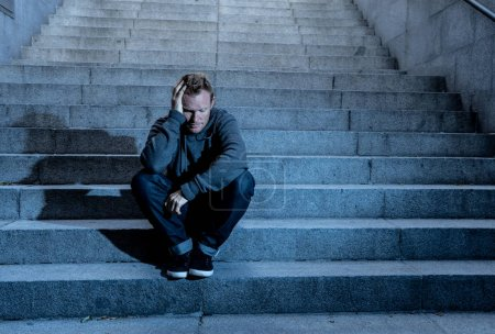 Photo for Young desperate jobless man in casual clothes abandoned lost in depression sitting on ground concrete stairs alone in grunge lighting in Emotional pain Loneliness Sadness Mental health concept. - Royalty Free Image