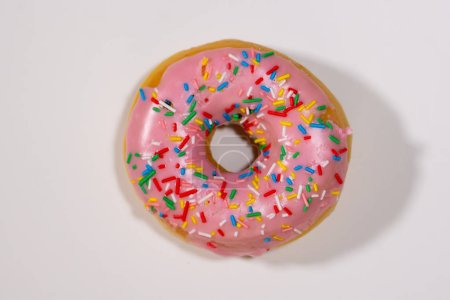 Photo for Close-up image of a delicious sugar glazed pink donut photo studio isolated on a white background In sweet treats unhealthy food and sugar addiction. - Royalty Free Image