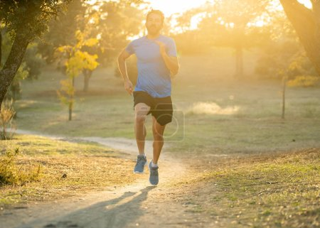 Photo for Happy runner in sportswear running training for Marathon outside in park at sunset on beautiful summer day in Sports Healthy lifestyle and Jogging Cross Country Training Workout Outdoors concept. - Royalty Free Image