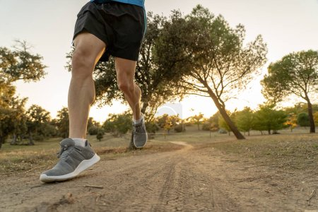 Photo for Young sport man running on countryside in cross country workout at summer sunset with harsh sunlight effect in at beautiful autumn park forest trail in fitness exercise and healthy lifestyle concept. - Royalty Free Image