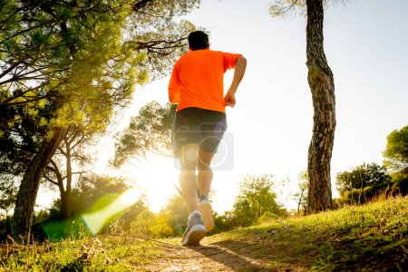 Photo pour Vue arrière de l'homme sport avec arraché les jambes athlétiques et musclés écoulage route nature au coucher du soleil automne en jogging d'entraînement à la campagne de remise en forme et concept de mode de vie sain. - image libre de droit