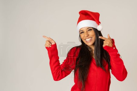 Foto de Alegre joven hermosa y sonriente en suéter de rojo y sombrero de santa, sonriente espacio copia juguetón y sosteniendo sobre fondo gris en feliz Navidad felices fiestas celebración y ventas concepto. - Imagen libre de derechos