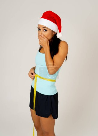 Photo for Sad unhappy young latin woman worried of gaining weight after Christmas in consequences of unhealthy eating lifestyle during christmas loss weight and diet isolated on white background. - Royalty Free Image