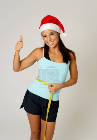 Photo for Young attractive latin sport woman in fitness clothes and santa claus Christmas hat holding measure tape on body waist in Wellness diet and weight loss resolution concept isolated on white background. - Royalty Free Image