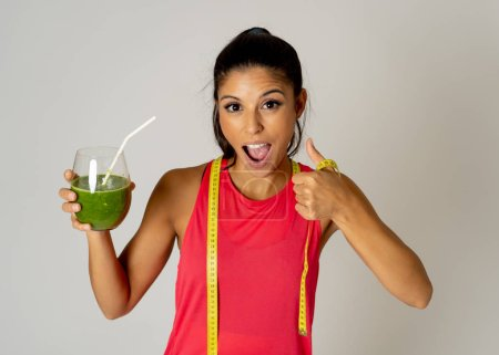 Photo for Healthy sport woman drinking fresh green detox cleanse spinach smoothie isolated on grey background in Fitness diet and healthy eating lifestyle concept. - Royalty Free Image