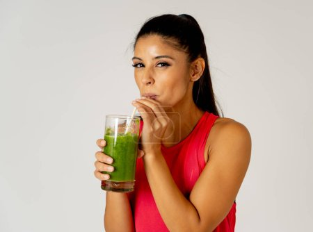 Photo for Fitness woman happy smiling holding glass of green vegetable smoothie after fitness running workout isolated on gray background in Beauty Health Fitness Diet Nutrition and healthy Lifestyle concept. - Royalty Free Image