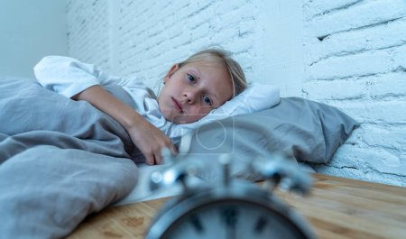 Photo for Sweet sleepless little girl lying sad in bed looking at alarm clock having to wake up but feeling tired sleepless in Troubles staying asleep Night Terrors Sleep disorder and Children Insomnia concept. - Royalty Free Image
