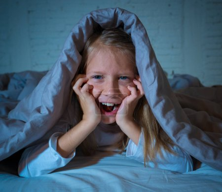 Photo for Cute asleep girl screaming and crying after frightening or upsetting dream covering herself with blanket in bed at night in mood dramatic lighting in Sleep terrors Nightmares and Sleeping disorders. - Royalty Free Image
