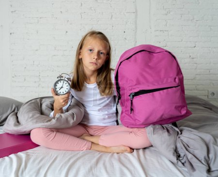 Photo for Beautiful blonde little girl sad sleepless and angry showing alarm clock time to get ready for school in difficulties waking up in the morning Children insomnia and sleeping disorders concept. - Royalty Free Image