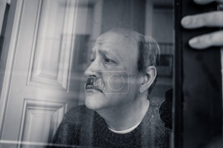 Photo for Senior man in his 60s feeling desperate sad looking throughout the balcony worried depressed thoughtful and lonely at home in Aging Depression Mental health Personal problems and Life style concept. - Royalty Free Image