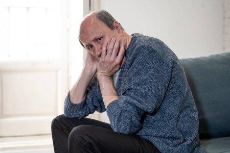 Photo pour Senior vieillard accablé souffrir seul à domicile sentiment confus triste seul sur canapé à la maison dans le concept de démence et d'Alzheimer veuf retraite vieillissement. - image libre de droit