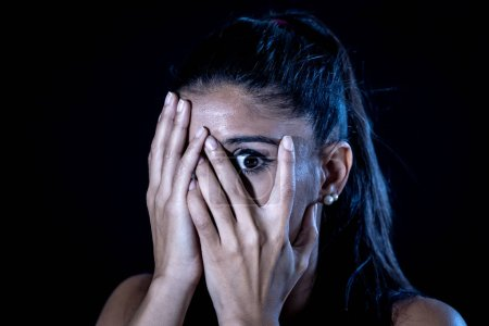 Photo for Close up portrait terrified young attractive latin woman looking frightened through her fingers in facial expressions and human emotions concept isolated on black background. - Royalty Free Image