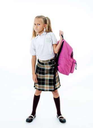 Photo for Young tired and sad cute school girl standing with a big heavy school bag on her back on a isolate white background for a back pain stress homework and back to school concept. - Royalty Free Image