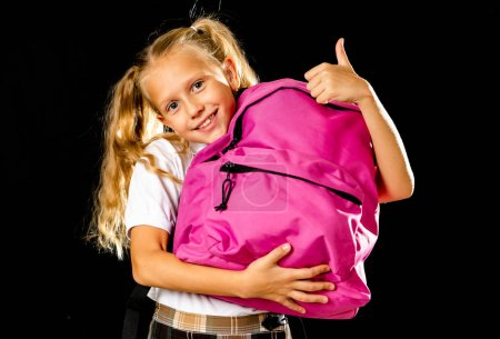 Photo for Pretty cute blonde hair girl with a pink schoolbag looking at camera showing thumb up gesture happy to go to school isolated on black background in back to school and children education concept. - Royalty Free Image
