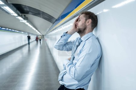 Photo for Desperate sad young businessman suffering emotional pain grief and deep depression sitting alone in tunnel subway in Stress life style Work problems failure Unemployment Mental health and Depression. - Royalty Free Image