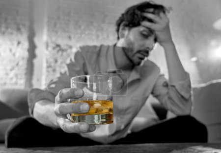 Photo for Drunk young man drinking alcohol at home felling lonely depressed and sick holding a glass of whiskey image in white and black and drink in color in Alcohol Addiction Social drug and Abuse concept. - Royalty Free Image