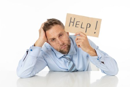 Photo for Young attractive frustrated and tired caucasian businessman holding help sign message exhausted and sad under pressure and stress isolated on white in unemployment depression and overwork concept. - Royalty Free Image