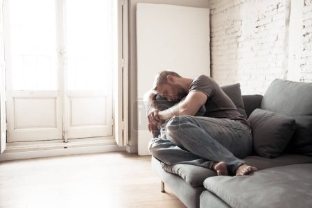 Photo for Unhappy depressed caucasian male sitting crying and lying in living room couch feeling desperate a lonely In stressed from work Unemployment Anxiety Heartbroken and depression Sadness concept - Royalty Free Image