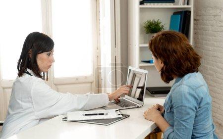 Photo pour Heureuse femme médecin expliquant le traitement et le diagnostic en montrant des résultats des tests sur ordinateur portable à la patiente en fonction de la clinique au concept de technologie et les gens de l'innovation médicale de la santé. - image libre de droit