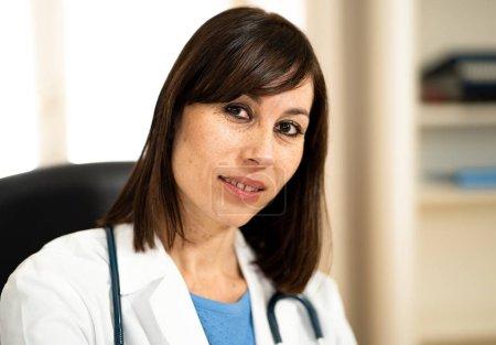 Photo pour Portrait de la souriante femme médecin travaillant sur ordinateur portable dans la salle de bureau clinique hôpital avec naturel à la recherche en soins de santé professionnels réussis et le concept de publicité d'assurance médical. - image libre de droit