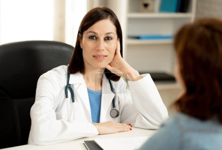 Photo for Smiling female doctor and happy patient talking and consulting in hospital clinic office in Health care, professional medical staff, happy hospital environment, Insurance and Medical trust concept. - Royalty Free Image